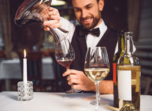 Man pouring scarlet wine in glass. Laughing sommelier is sitting at table and poring red nectar in wineglass Stock Photography