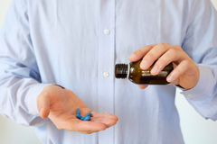 Man pouring some pills from a bottle. Man pouring some pill from a bottle royalty free stock photography