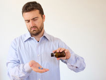 Man pouring some pills from a bottle Stock Photography