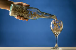 Man pouring string into a wineglass. Man pouring a tangled mass of string from a transparent wine bottle into a wineglass in a conceptual image over blue with Royalty Free Stock Photos