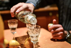 Man pouring strong alcoholic drink vodka in glass Royalty Free Stock Image