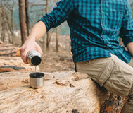 Man pouring tea in the forest. Unrecognizable hiker young man pouring tea from thermos to cup in the forest outdoor Royalty Free Stock Photo