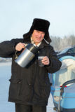 Man pouring tea outdoor. Man pouring tea from thermos outdoor in winter, Siberia, Russia Royalty Free Stock Photo