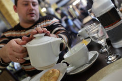 Man pouring tea in cafe Stock Images