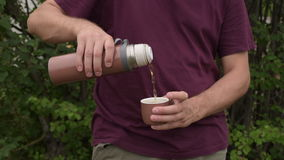 Man pouring tea from thermos into cup stock video