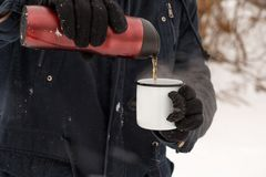 A man is pouring tea from a thermos into a cup in the winter for. Est Royalty Free Stock Photo