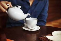 Man pouring tea into a white china tea cup. Man pouring white tea into a white china tea cup in cafe stock images