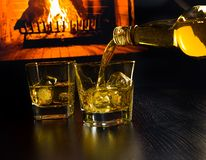Man pouring two glasses of whiskey with ice cubes in front of the fireplace Royalty Free Stock Photography