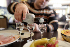 Man pouring vodka in taverna Stock Photo