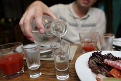 Man pouring vodka from a carafe Stock Images