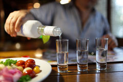 Man pouring vodka in pub Royalty Free Stock Photography