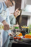 Man pouring white wine in glasses while cooking with woman at kitchen Stock Images
