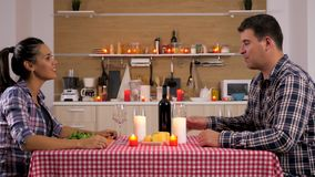 Man pouring wine to his girlfriend. At candle light dinner in the kitchen. Dolly slider 4K footage stock footage