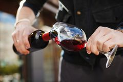Man pouring wine into wineglass, male hand holding bottle. Of red expensive alcoholic beverage, closeup photo Royalty Free Stock Photo