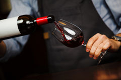 Man pouring wine into wineglass, male hand holding bottle. Of red expensive alcoholic beverage, closeup photo Stock Photography