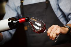 Man pouring wine into wineglass, male hand holding bottle. Of red expensive alcoholic beverage, closeup photo stock photo