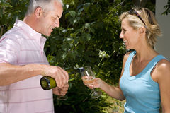 Man pouring wine for woman in garden, smiling, side view Stock Photos