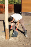 Man pours a bucket of cement into hole Stock Photo