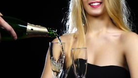 Man pours champagne into two glasses. Slow motion stock video footage