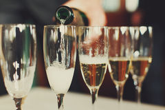 Man pours champagne in wineglasses Stock Photos