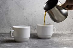 Man  pours coffee from cezve. Two cups of coffee, man  pours coffee from cezve , concrete background Royalty Free Stock Image