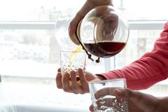 A man pours a drink. A man pours coffee for a sample from a decanter into faceted transparent glasses Stock Photography