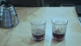 A man pours a drink into glasses. Close-up. A man pours a drink into two glasses from glass teapot. He take away the teapot and take a glasses into the hands stock video footage