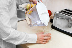Man pours filtered water. Into the glass Royalty Free Stock Photo
