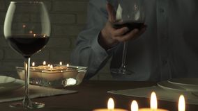 Man pours glass of red wine at candlelight romantic evening slow motion stock footage video stock footage