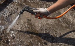Man pours from the hose the ground in the garden. Man pours from the hose a ground in the garden royalty free stock photography