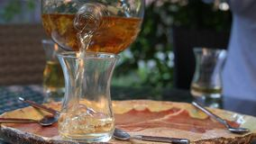 A man pours hot tea from a glass teapot into a transparent mug. Herbal Tea. A man pours hot tea from a glass teapot into a transparent mug. Herbal Healthy Tea stock video footage