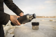 Man pours hot tea from a thermos into a cup Stock Images