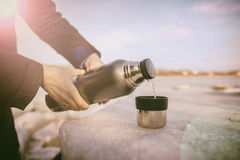 Man pours hot tea from a thermos into a cup Stock Photography