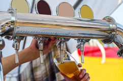 Man pours a light beer from kegs into glass Stock Images