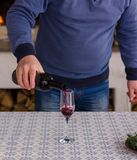 The man pours a red wine in a glass against the burning flame of the fireplace. stock images