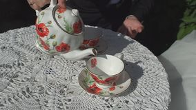 Man pours tea into a cup with a teapot, seated in cafe. stock video