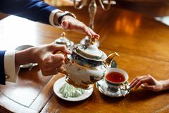 A man pours tea into a refined dish to a woman while in a restaurant at a wooden table. royalty free stock image