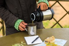 Man pours tea from a thermos. On a picnic in autumn park Royalty Free Stock Image