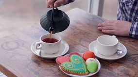 A man pours tea. Vintage table, collorful cookies. stock video footage