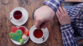 A man pours tea. Vintage table, collorful cookies. stock video