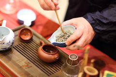 Man pours tealeafs by bamboo Tea Scoop Royalty Free Stock Images