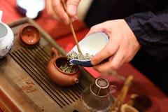 Man pours tealeafs into teapot Stock Photos