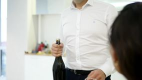 Man pours two glasses of champagne to celebrate moving into new home with girlfriend.  stock video