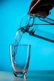 Man pours water from glass. Into glass on blue background in studio Royalty Free Stock Images