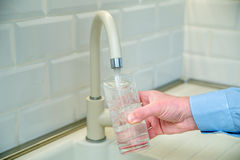 Man pours water into a glass. From a faucet Royalty Free Stock Image