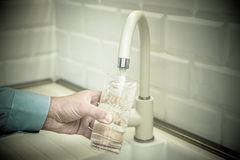 Man pours water into a glass. From a faucet Royalty Free Stock Photos
