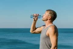 A man drinking and pours water on his face from bottle on the ocean, refreshing after a workout stock photo