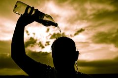 Man pours water on his head in the sunset.  Stock Image