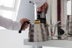 Man pours water. A person gently pours hot water into a metal kettle Stock Photos