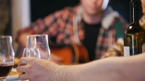 A man pours wine. The camera changes focus to another man who plays the guitar. Close up stock video